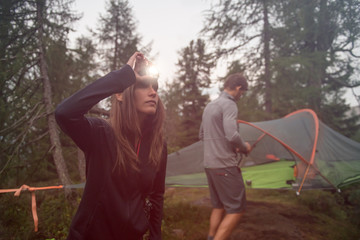 Woman turning on headlamp flashlight near hanging tent camping. Group of friends people summer adventure journey in mountain nature outdoors. Travel exploring Alps, Dolomites, Italy. Wall mural