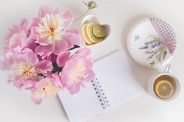 Bouquet of peonies, tea with lemon, notebook , photo in gentle colors. Good morning. Have a nice day! Place for text