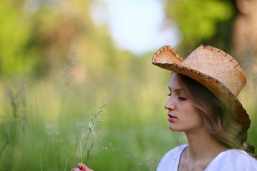 Feminine beautiful woman in green field, sitting in grass, positive, daisies, closed eyes, enjoy, outdoor, white dress, cowboy , hat, copy space, summer background, close up