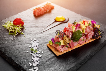 fresh tuna tartar with salt and herbs, studio shot. Fish tartar on black shale.