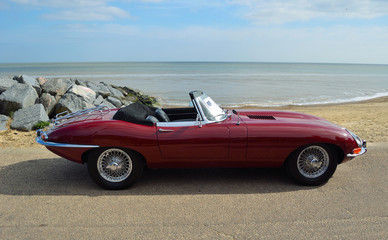 Classic Dark Red British Sports Convertible Motor Car Parked on Seafront Promenade.