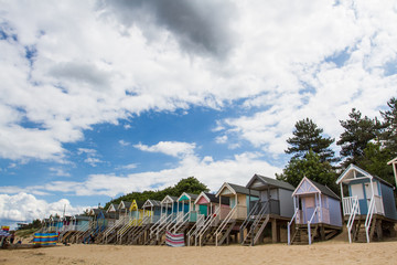 Rows of colourful wooden beach huts on a sandy beach in Norfolk, UK under a blue sky and summer sunshine.