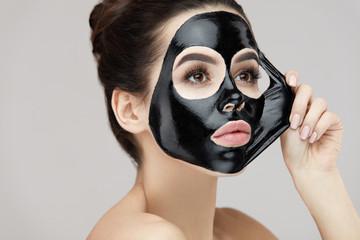 Woman Face Mask. Closeup Beautiful Girl Removing Black Mask