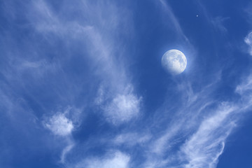 A half of the moon in clouds . Peaceful sky . Beautiful clouds . Eclipse of the moon