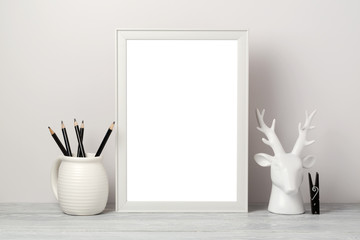 White frame mock up with pencil and decor deer. Modern stylish interior background for social media and marketing.
