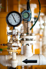 pressure gauge,analog pressure gauge measuring gas pressure. Pipes and valves at oil and gas industrial plant.