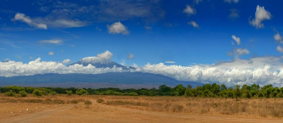 Kilimanjaro mountain Tanzania snow capped under cloudy blue skies captured whist on safari in Africa Kenya.