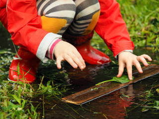 Child plays a puddle. Girls hands. Bright clothing - rubber boots and jacket. Summer, green grass