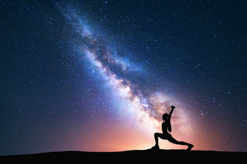 Milky Way with silhouette of a standing woman practicing yoga on the field. Beautiful landscape with meditating girl against night starry sky with bright milky way. Amazing galaxy. Universe. Fitness