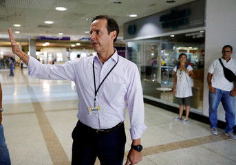 Former president of Bolivia Quiroga gestures as he arrives at Caracas airport ahead of an unofficial referendum called by the opposition against Venezuelan President Maduro's government