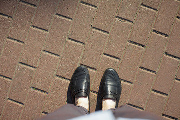 Top view of casual dressed businessman legs wearing black shoes walking go to dream. Summer theme