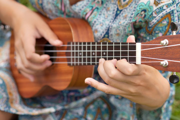 Closeup photo of young woman playing on Ukulel