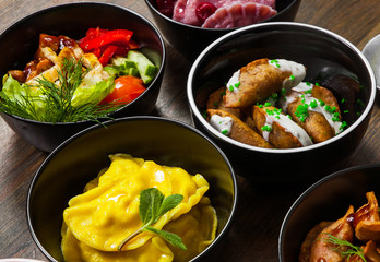 Set of different salad, dumplings and ravioli on a wooden table