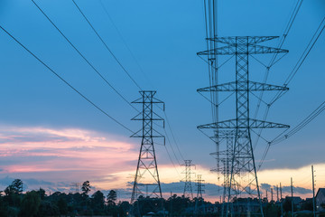 Group silhouette of transmission towers (power tower, electricity pylon, steel lattice tower) at twilight in Humble, Texas, US. Texture high voltage pillar, overhead power line, industrial background.
