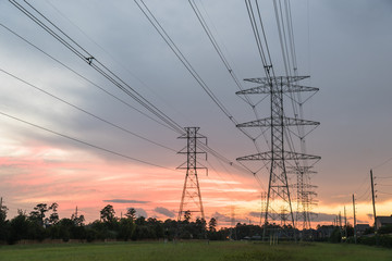 Group silhouette of transmission towers (power tower, electricity pylon, steel lattice tower) at sunset in Humble, Texas, US. Texture high voltage pillar, overhead power line, industrial background.