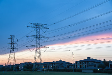 Group silhouette transmission towers (steel lattice/power tower, electricity pylon) next to apartment complex at sunset in US. Texture high voltage pillar, overhead power line, industrial background.