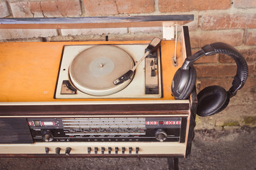 Old vintage antique radio with music record player and headphones on red brick wall background. .