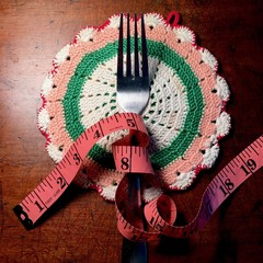 Pink tape measure coiled around a fork on vintage crocheted doily. Illustrates weight loss goals, diet and exercise, food and nutrition, eating disorders.