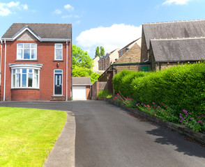 Typical english single family house built of red bricks, with a large driveway