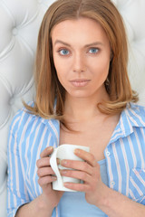 beautiful young woman with white cup