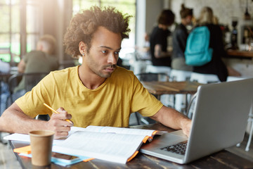 University student with dark skin and African hairstyle sitting at cafe working with books and notebook while getting prepared for exam finding necessary information in internet having serious look