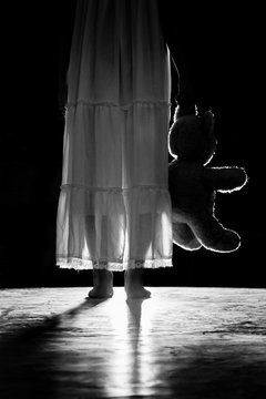 a girl holding a teddy bear in the darkness