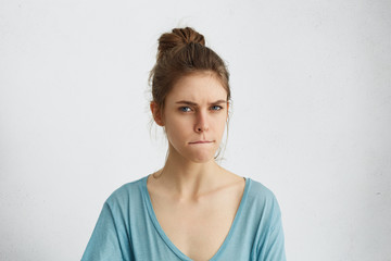 Serious angry woman frowning her face pressing lips togehter with anger trying to control herself and her emotions not showing her annoyance and anger. Dissatisfied young female in casual clothes