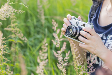 Hands of a girl holding a vintage camera on a background of high green grass