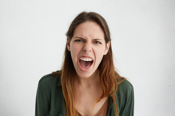 Mad Caucasian woman screaming loudly opening her mouth frowning face with anger demonstrating her negative emotions. Furious baeutiful young woman shouting at her husband who came late home.