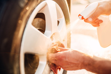 Male hands cleans disk with car rim cleaner