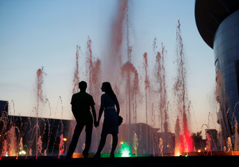 A couple is silhouetted in front of a musical fountain at the Millennium Square in Saransk