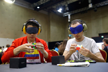 Competitors solve Rubik's cubes as they prepare for the world's largest Rubik's Cube championship in Aubervilliers