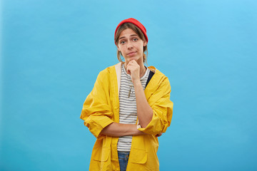 Portrait of pretty female dressed in yellow raincoat and red hat keeping her hand on chin looking directly into camera going to have walk in forest or to river isolated over blue studio background