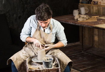 pottery, workshop, ceramics art concept - young male master works with hands and potter wheel, brunette male fingers sculpt some new jug from raw clay with water, close-up