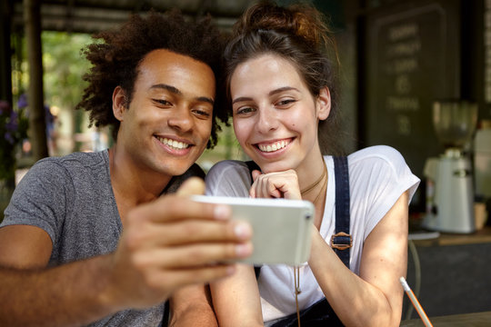 Portrait of black Afro American male and his European girlfriend sitting close to each other at cozy restaurant looking with smiles in camera of their smart phone making selfie. People, lifestyle