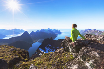 Hiker on top of mountain with view of norwegian fjord Wall mural