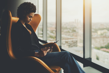 Cute pensive afro american student is sitting on armchair in front of window of skyscraper and having online conversation with her curator during probation period in office via digital tablet