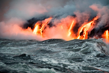 Molten lava flowing into the Pacific Ocean on Big Island of Hawaii at sunrise
