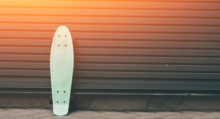 a skateboard leaning against wall, empty space at the right for custom text