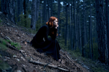 Beautiful young woman in a long black dress in the forest
