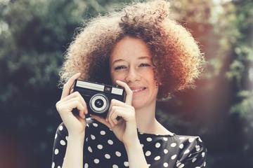 jeune femme rousse avec appareil photo vintage dans nature