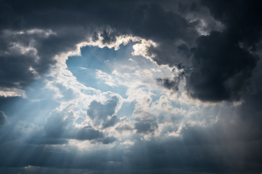 sun rays shining through dark clouds after strom