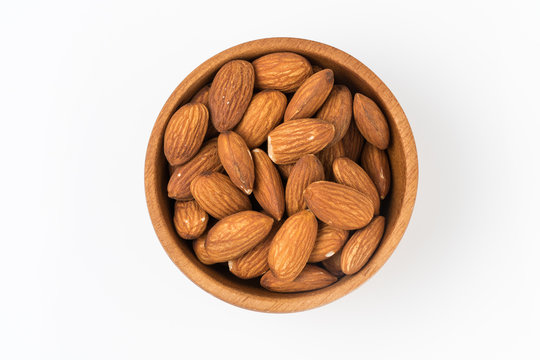 Almond in wooden bowl isolated on white background. Top view