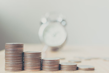 Concept business finance save money, Coins stack on wood table with blurred alarm clock