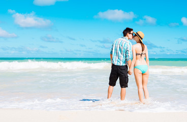 Romantic beach getaway. Young couple kissing and holding hands on a tropical beach. (location Hawaii)