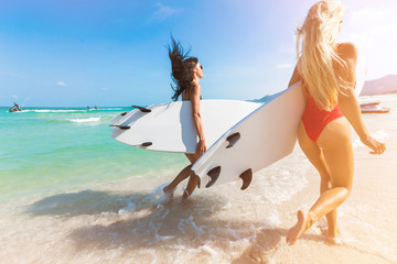 Two beautiful amazing tanned girls are surfing, blonde and brunette, sports ideal figures, sexy swimsuits, a healthy lifestyle, long hair, run with surfs under your arm in the sea, best friends summer