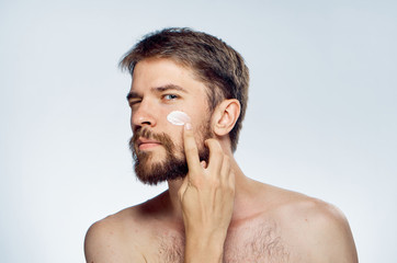 Young guy with beard on white isolated background applies cosmetic cream