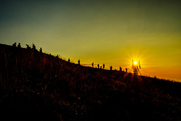 silhouette of Travel team Group of friends on the top of mountain looking to sunset view