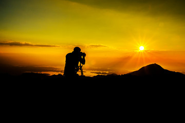 silhouette of photographer on the top of mountain takephoto to sunset river clounds sky view, Thailand