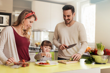 Young family preparing salad together